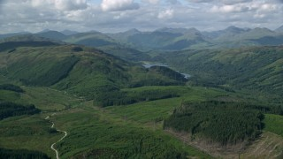 AX110_045 - 6K stock footage aerial video of tree-covered mountains and Loch Chon, Scottish Highlands, Scotland