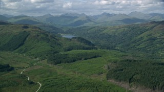 AX110_046 - 6K stock footage aerial video of tree-covered mountains around Loch Chon, Scottish Highlands  Scotland