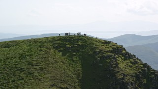 AX110_050 - 6K stock footage aerial video flyby hikers on Ben Lomond mountain, Scottish Highlands, Scotland