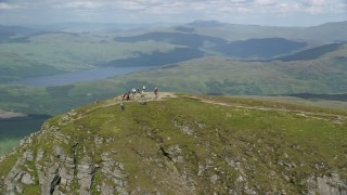AX110_052 - 6K stock footage aerial video of flyby hikers on Ben Lomond mountain peak in the Scottish Highlands, Scotland