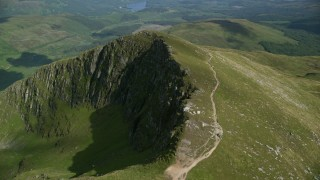 AX110_053 - 6K stock footage aerial video of flyby dirt path on Ben Lomond mountain peak, Scottish Highlands, Scotland