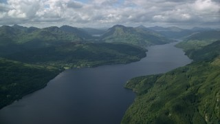 AX110_059 - 6K stock footage aerial video of calm waters of Loch Lomond, Scottish Highlands, Scotland