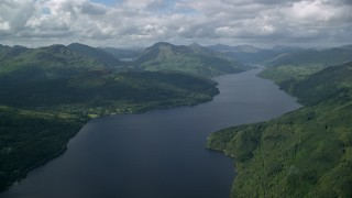 AX110_060 - 6K stock footage aerial video of green mountains and calm waters of Loch Lomond, Scottish Highlands, Scotland
