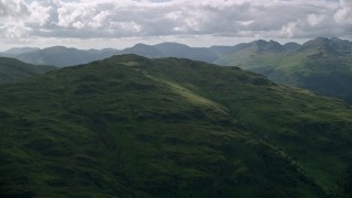 AX110_061 - 6K stock footage aerial video approach a green mountain peak, Scottish Highlands, Scotland