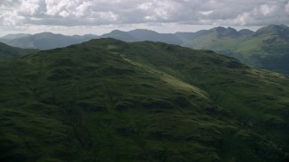 AX110_062 - 6K stock footage aerial video approach a green mountain peak, Scottish Highlands, Scotland