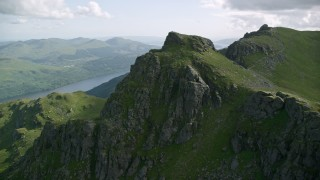 AX110_085 - 6K stock footage aerial video of flying away from a mountain peak, The Cobbler, Scottish Highlands, Scotland