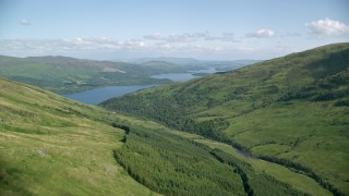 AX110_099 - 6K stock footage aerial video approach blue waters of Loch Lomond from green peaks, Scottish Highlands, Scotland