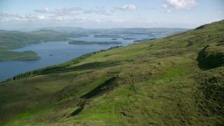 AX110_102 - 6K stock footage aerial video approach Loch Lomond from a lush green mountain, Scottish Highlands