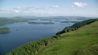 AX110_103 - 6K stock footage aerial video approach blue waters of Loch Lomond, Scottish Highlands