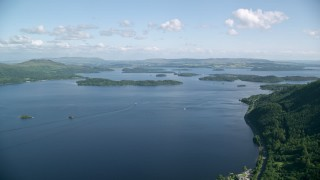 AX110_104 - 6K stock footage aerial video of the blue waters of Loch Lomond and tiny islands, Scottish Highlands, Scotland