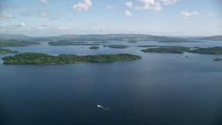 AX110_105 - 6K stock footage aerial video approach tree-covered islands in Loch Lomond, Scottish Highlands, Scotland