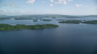 AX110_106 - 6K stock footage aerial video pan across tree-covered islands in Loch Lomond, Scottish Highlands, Scotland