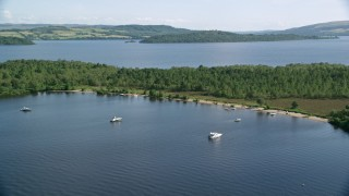 AX110_109 - 6K stock footage aerial video approach boats along a small island beach, Loch Lomond, Scottish Highlands, Scotland