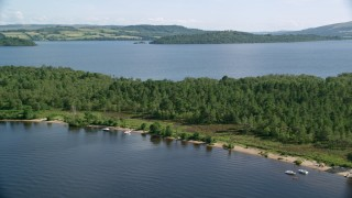 AX110_110 - 6K stock footage aerial video fly over small island beach with trees, Loch Lomond, Scottish Highlands, Scotland
