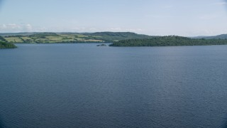AX110_111 - 6K stock footage aerial video approach islands in the blue waters of Loch Lomond, Scottish Highlands, Scotland