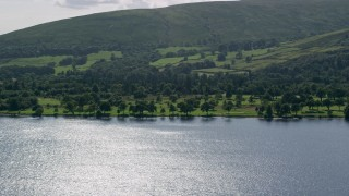 AX110_112 - 6K stock footage aerial video of a waterfront golf course on Loch Lomond in Luss, Scottish Highlands, Scotland
