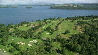 AX110_116 - 6K stock footage aerial video of orbiting Loch Lomond Golf Course along the water, Luss, Scottish Highlands, Scotland