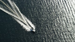 AX110_121 - 6K stock footage aerial video of tracking fishing boat on calm blue waters, Loch Lomond, Scottish Highlands, Scotland