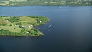 AX110_124 - 6K stock footage aerial video of orbiting sailboats along a Loch Lomond island, Scottish Highlands, Scotland