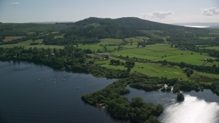 AX110_125 - 6K stock footage aerial video of farms beside Loch Lomond, Arden, Scottish Highlands, Scotland