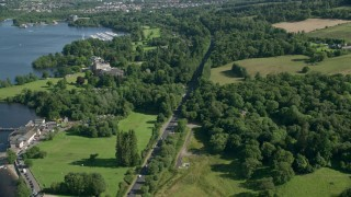 AX110_127 - 6K stock footage aerial video fly over A82 Highway along the water and through trees, Alexandria, Scotland