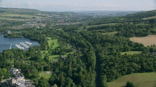 AX110_128 - 6K stock footage aerial video approach Alexandria while following the A82 Highway and trees, Scotland