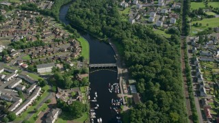 AX110_132 - 6K stock footage aerial video fly over small bridges on River Leven in a small town, Alexandria, Scotland