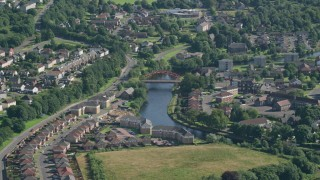 AX110_133 - 6K stock footage aerial video approach small bridge on River Leven through residential neighborhood, Alexandria, Scotland