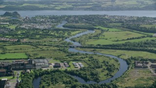AX110_136 - 6K stock footage aerial video approach River Leven toward a waterfront town, Dumbarton, Scotland