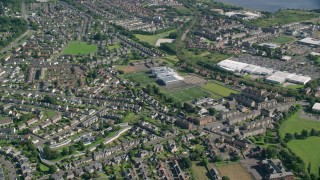 AX110_138 - 6K stock footage aerial video approach and tilt to residential neighborhood, Dumbarton, Scotland