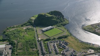 AX110_140 - 6K stock footage aerial video of orbiting Dumbarton Castle and soccer stadium by the water, Scotland