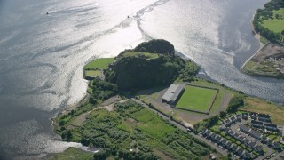 AX110_141 - 6K stock footage aerial video of Dumbarton Castle and soccer stadium beside the water, Scotland