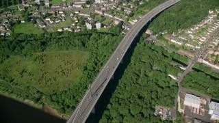 AX110_145 - 6K stock footage aerial video of a bird's eye orbit of Erskine Bridge by residential neighborhoods, Glasgow, Scotland
