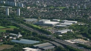AX110_152 - 6K stock footage aerial video of M8 Freeway near warehouse buildings, Glasgow, Scotland