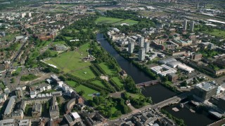 AX110_160 - 6K stock footage aerial video of monument and museum in Glasgow Green park by River Clyde, Scotland