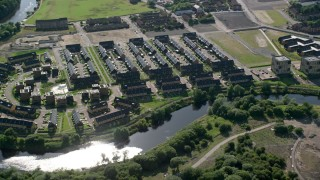 AX110_189 - 6K stock footage aerial video of riverfront row houses along River Clyde, Glasgow, Scotland