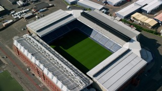 AX110_201 - 6K stock footage aerial video approach Ibrox Stadium, tilt to bird's eye of soccer field, Glasgow, Scotland