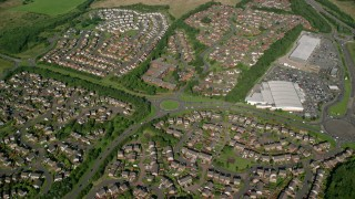 AX110_218 - 6K stock footage aerial video of a roundabout and residential neighborhood, Glasgow, Scotland