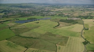 AX110_219 - 6K stock footage aerial video approach farms, fields, and rural neighborhoods, Glasgow, Scotland