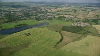 AX110_220 - 6K stock footage aerial video approach farming fields and rural neighborhoods outside of Glasgow, Scotland