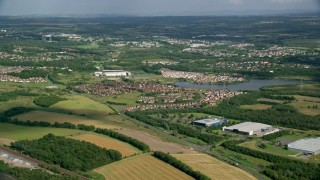 AX110_227 - 6K stock footage aerial video of lakefront homes and farm fields, Broadwood Loch, Scotland