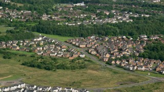 AX110_228 - 6K stock footage aerial video of suburban homes and trees, Cumbernauld, Scotland