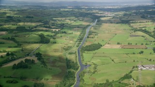 AX110_230 - 6K stock footage aerial video of farm fields around a river, Cumbernauld, Scotland