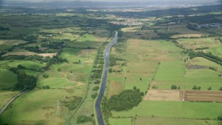 AX110_231 - 6K stock footage aerial video of following a river through farm fields, Cumbernauld, Scotland