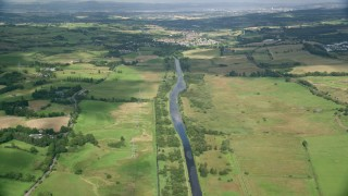 AX110_232 - 6K stock footage aerial video of following a river through farm fields, Cumbernauld, Scotland