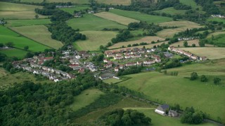 AX110_233 - 6K stock footage aerial video of rural homes surrounded by farmland, Cumbernauld, Scotland