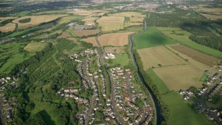 AX111_004 - 6K stock footage aerial video fly over village homes and farms around a river, Bonnybridge, Scotland