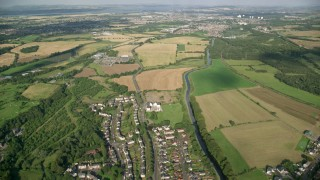 AX111_005 - 6K stock footage aerial video fly over village homes and farm fields by a river, Bonnybridge, Scotland
