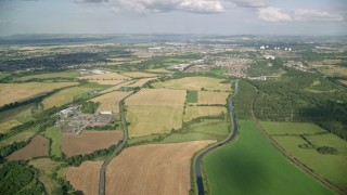 AX111_006 - 6K stock footage aerial video of farm fields and river while approaching Falkirk, Scotland