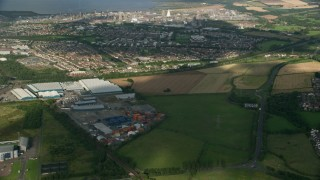 AX111_008 - 6K stock footage aerial video of warehouses and suburban neighborhoods near gas power plant, Falkirk, Scotland